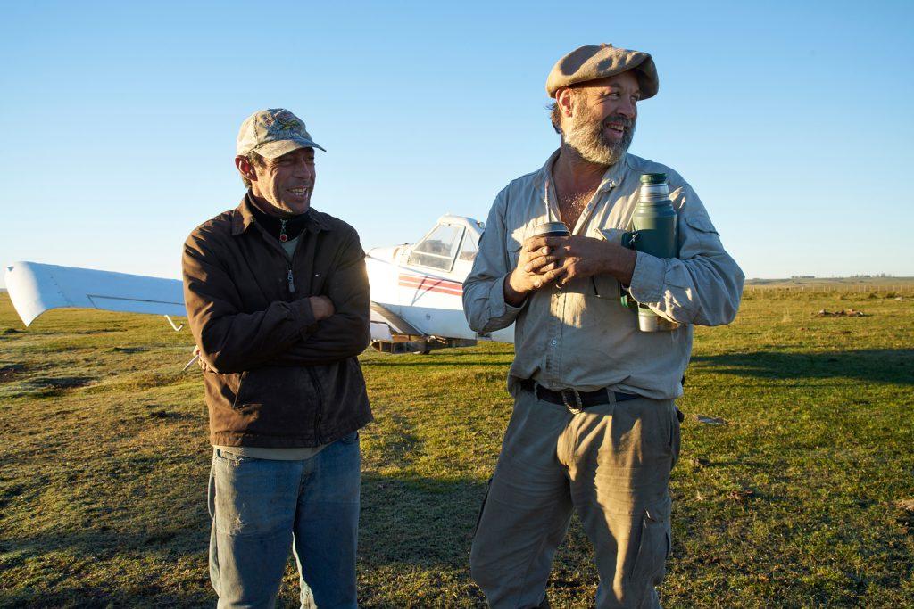 Farm Tres Rincones bei Artigas, Martin Echenagusia, der Besitzer ( rechts im Bild mit Mathetee ) und sein Pilot, der an diesem Tag zum Düngen der Weiden gekommen ist, Uruguay Mai 2017